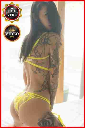 Sandy escort Milano con un completino giallo e i tatuaggi in bella vista.