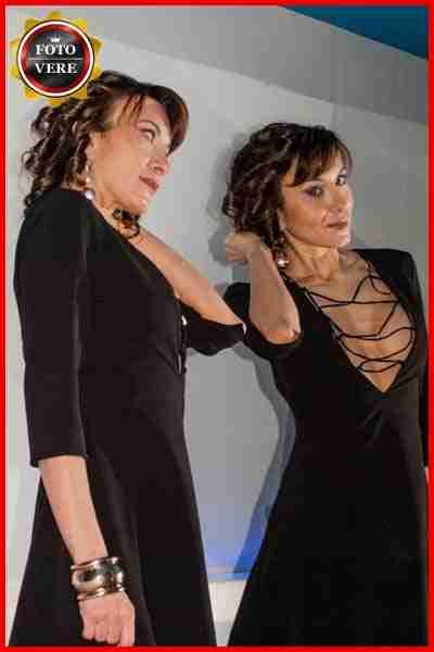 Celine top class escort Bergamo indossa una abito nero molto scollato. Magica Escort