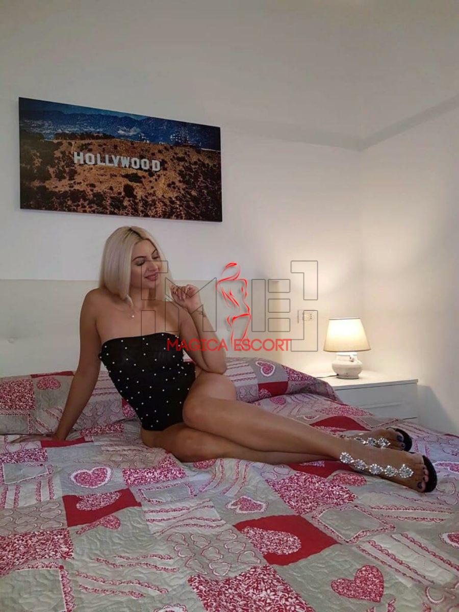 Model top class Erica seduta nel letto con in una posa dolcissima. Magica Escort.